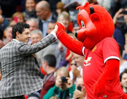 The famous manchester united fan and golf supremo high fives the Red Devil mascot.