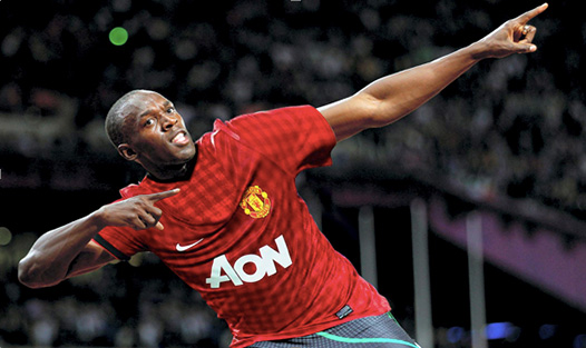 Celebrity fan Bolt poses in Manchester United Jersey